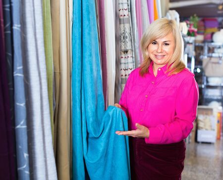 Positive cheerful smiling mature woman seller showing curtain in the curtains shop