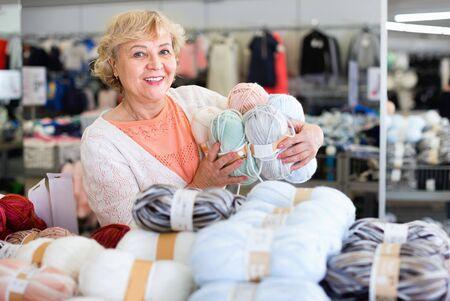 Happy smiling mature woman buyer choosing colored yarn for knitting on sale 版權商用圖片
