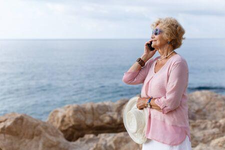 Positive mature woman talking on mobile phone and relaxing at seashore 版權商用圖片
