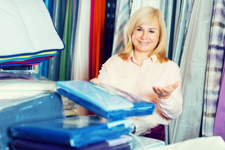 Portrait of smiling mature female standing in the textile store