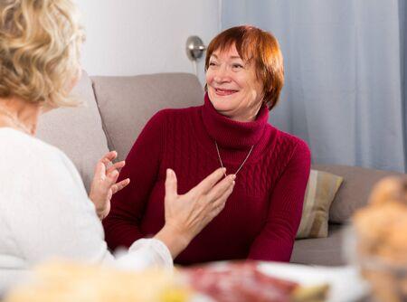 Portrait of cheerful mature females talking at home on cozy sofa 版權商用圖片
