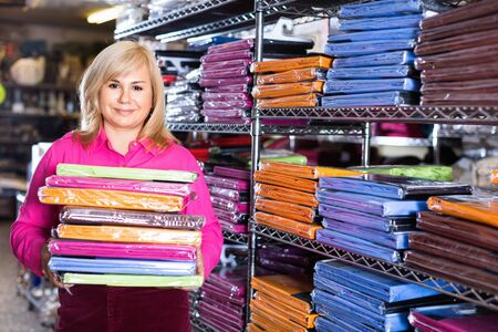 Portrait of cheerful positive  mature woman showing stack of bedsheet in the textile shop