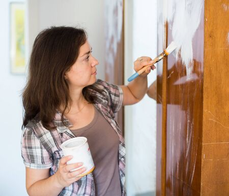 Woman is painting old cupboard in time repairs in the house.