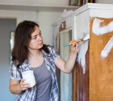 Happy woman makes repairs in the apartment and  paints closet