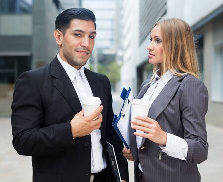Businesswoman and her partner are standing with folder and coffee near the office. Banque d'images
