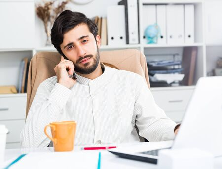 Young handsome male office worker talking on mobile phone at table in office