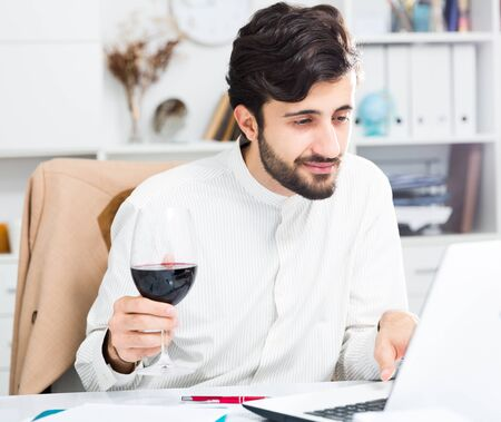 Cheerful brunette man holding glass of red wine and working at laptop in office