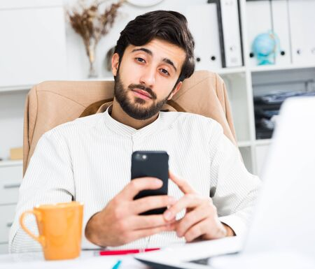 Young positive office worker using his smartphone at workplace in office