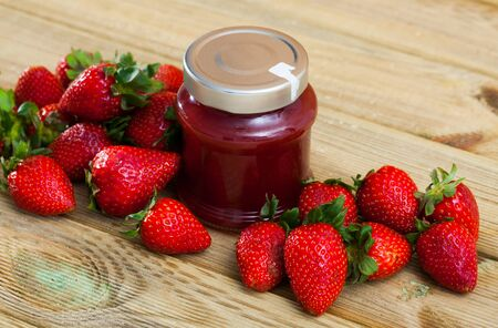 Glass jar of homemade strawberry jam with fresh berries on background