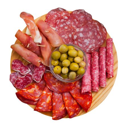 Top view of coldcuts of delicious Spanish cured jamon and piquant sausages garnished with green olives on wooden board. Isolated over white background Stock Photo
