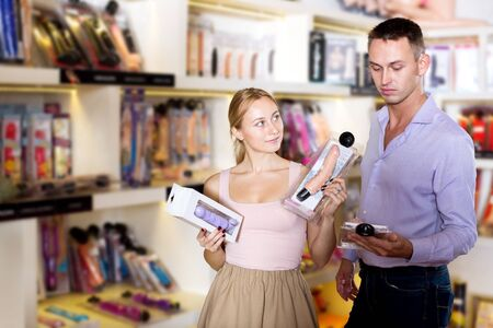 Portrait male consultant advising customer shopping sex toy in store for adults
