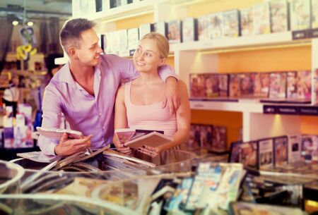 Happy  family couple selecting erotic video and smiling in store Stock Photo