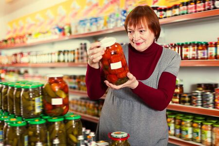 Smiling woman buyer choosing canned jar of tomatoes at the supermarket Foto de archivo