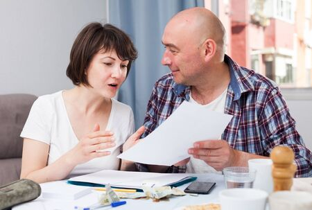 Portrait of family couple with financial documents and money at kitchen table