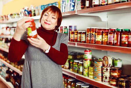 Pleasant  female buyer choosing canned jar of tomato paste at the supermarket