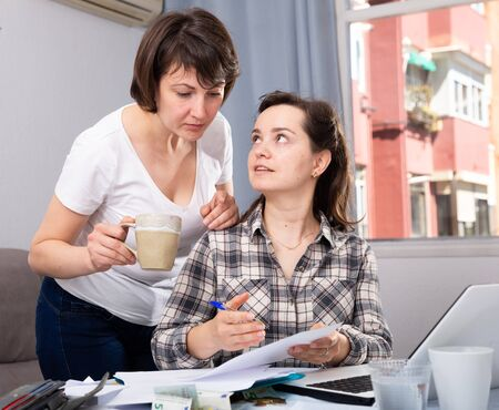 Women working with documents while working at laptop at home interior