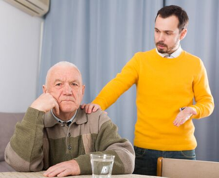 Aged father and son are serious talk and solve family problems Reklamní fotografie