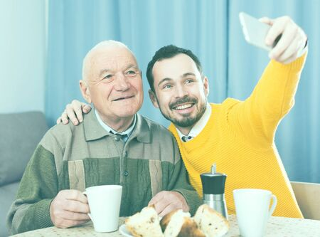 Aged father and young son doing selfie home at table