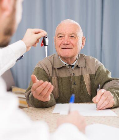 Mature man preparing new car papers at home