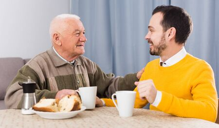 Elderly father and son together having breakfast at table and friendly communicate Reklamní fotografie