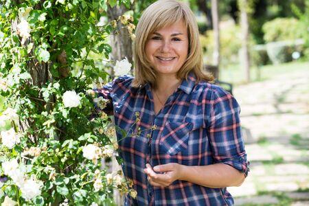Closeup retrato de mujer madura rubia alegre disfrutando de su tiempo en el jardín el día de verano