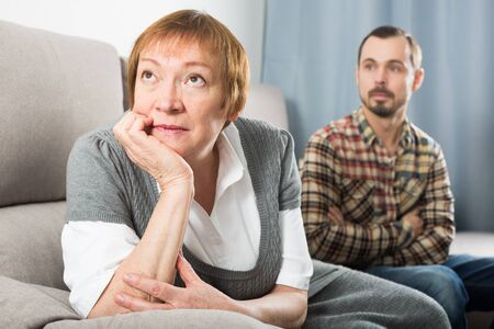Mature mother quarrelling with her adult son at home