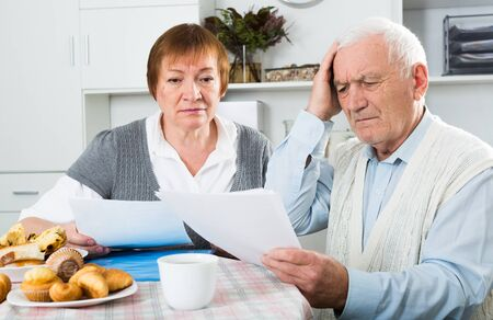 Elderly couple studying agreement conditions before signing at home Banque d'images