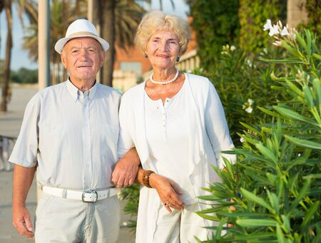 portrait of mature happy couple man in hat and woman on nature