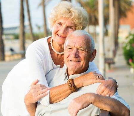 Portrait of old smiling male and female hugging on the nature
