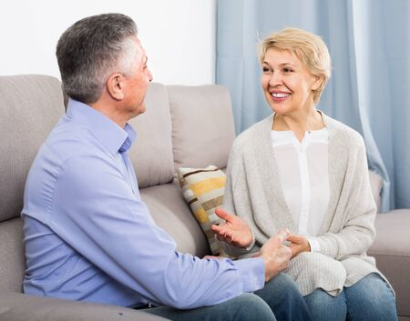 friendly mature married couple in cozy house are warmly reconciled after quarrel
