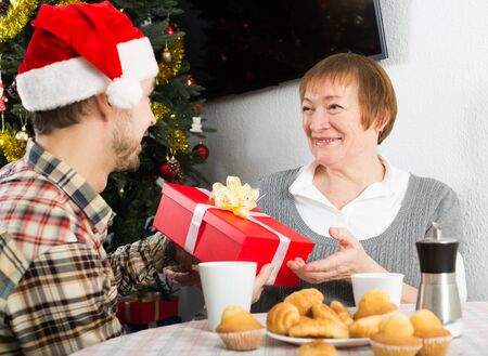 Adult son and mother presenting gifts during Christmas at home