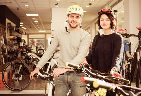 Ordinary couple in helmet standing near sport bicycle in bicycle store 免版税图像 - 125152997