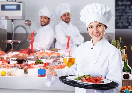 smiling woman chef standing with serving tray in fish restaurant Фото со стока - 125153007
