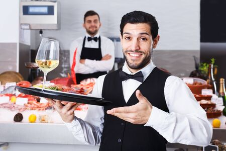 Handsome bearded waiter standing with serving tray in seafood restaurant Stock fotó