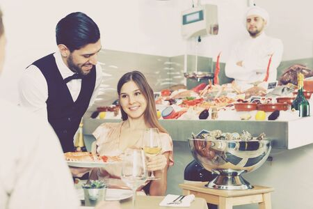Girl nicely in fish restaurant spending time with man colleague over dinner Banque d'images