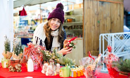 Happy young girl buying floral compositions at Christmas market Banque d'images