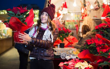 Portrait of smiling female teenage customer buying poinsettia decorations for Christmas outdoor