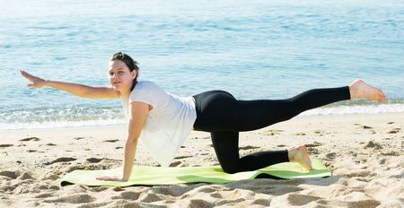 Female 20-30 years old is practicing yoga on the beach.