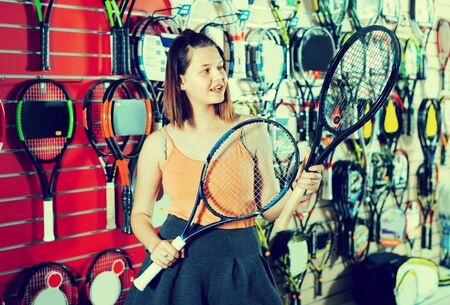 Young happy cheerful girl standing in t-shirt in sporting goods store with racket