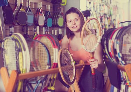 Portrait of happy young female teen choosing wood racket for squash