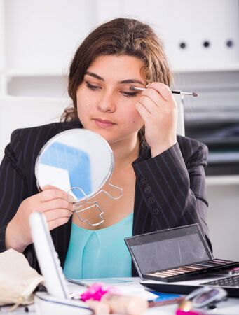 Person is making makeup before meeting in office.