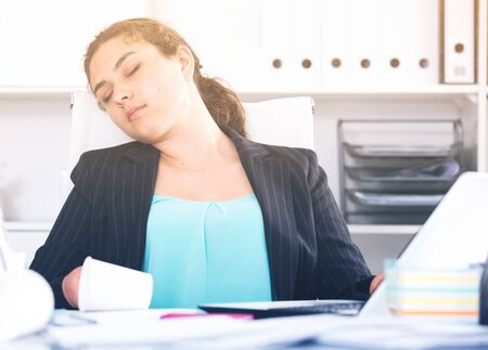 Female manager is sleeping at work after putting the reports in the office.