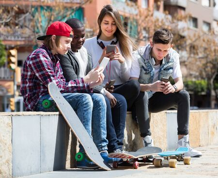 Ordinary friends with smartphones in spring day outdoors