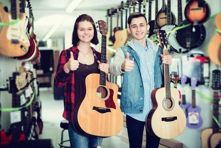 Happy young teenage boy and girl choosing best acoustic guitar in guitar shop