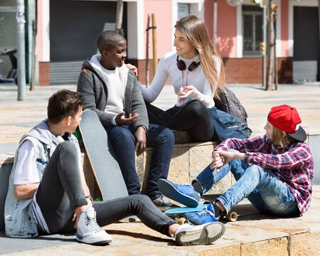 Group of cheerful positive  teenage friends relaxing and chatting in town square