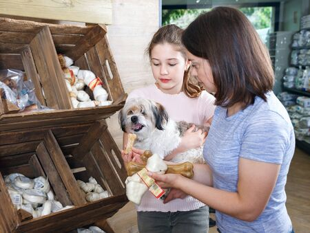 Cheerful  glad mother with teen daughter choosing dog treats for their puppy in pet supplies store Фото со стока