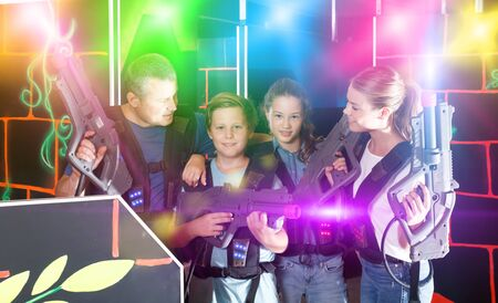 Happy teens and theirs parents with laser guns during laser tag game indoors