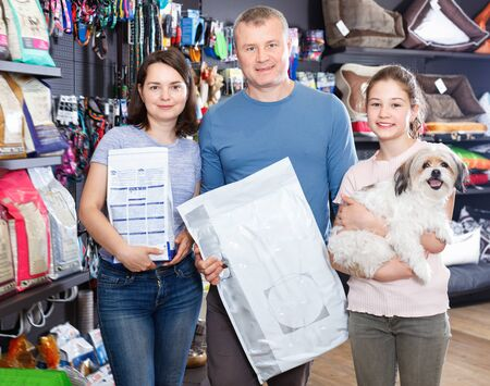 Portrait of cheerful positive glad family with their puppy during visit of pet shop Фото со стока