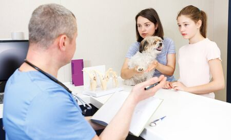 Worried young mother and daughter with their puppy visiting veterinarian clinic