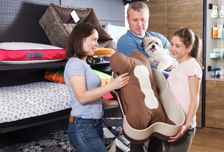 Happy attractive young family with preteen daughter visiting pet shop in search of accessories for their dog